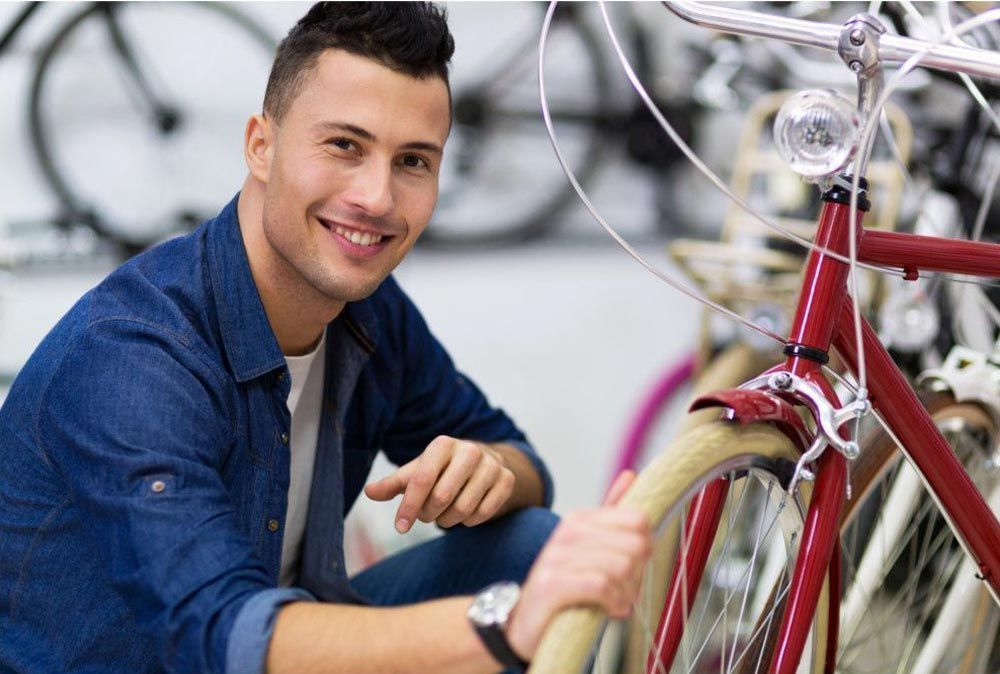 Happy guy who maintains a bike easily thanks to RENT-ALL bike rental management software