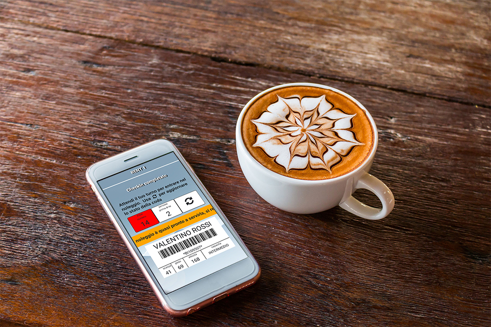 Cup of cappuccino with cell phone on the side that monitors your turn thanks to the RENT-ALL checkin